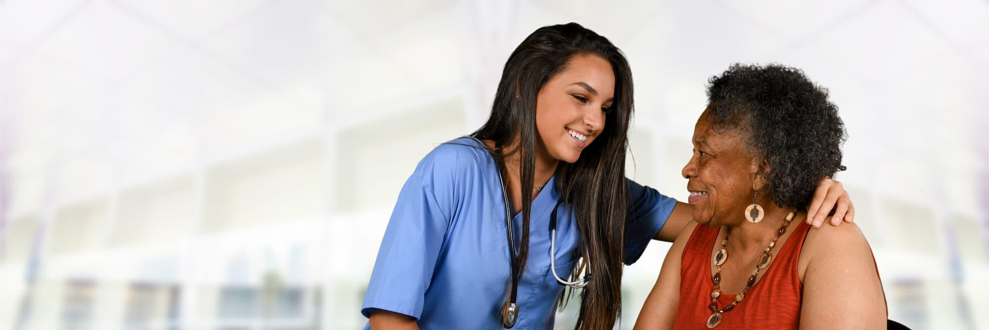 Nurse in scrubs putting her arm around an elderly woman.