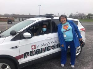 Aquinas employee posing with hospital security officer in a cruiser.
