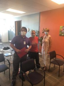 Aquinas employees smiling behind surgical masks.