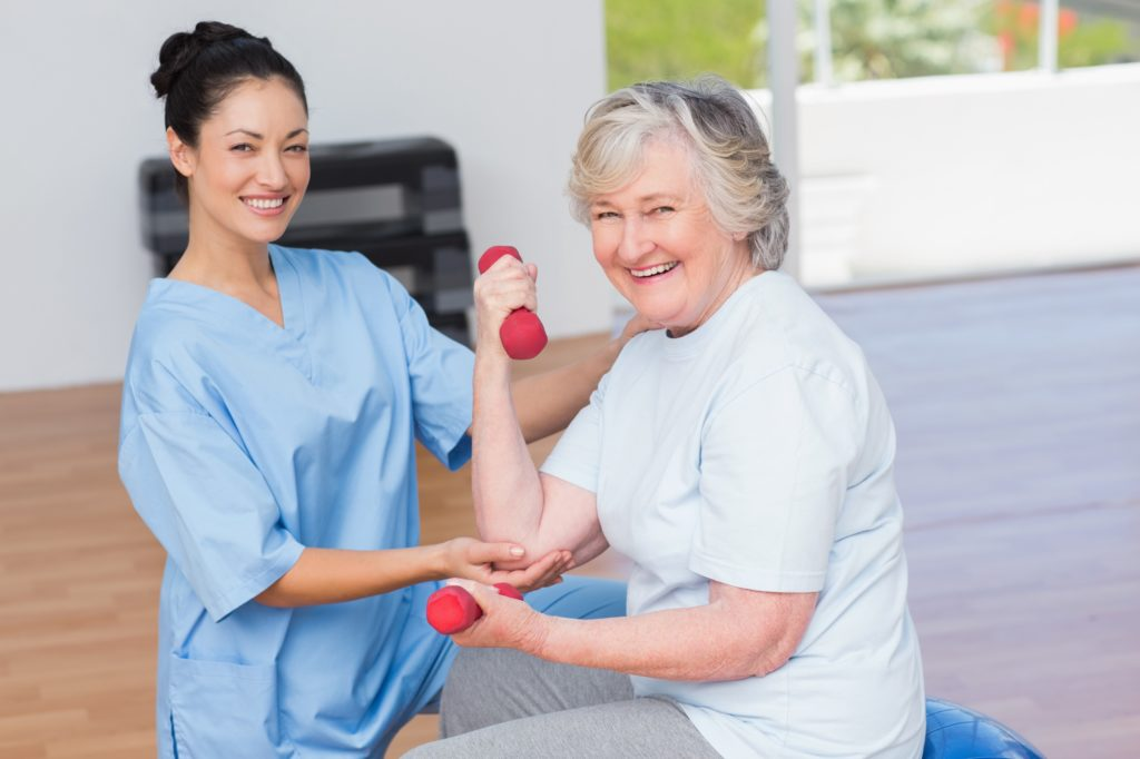 Nurse in scrubs helping an eldery lady with her phsycial therapy.