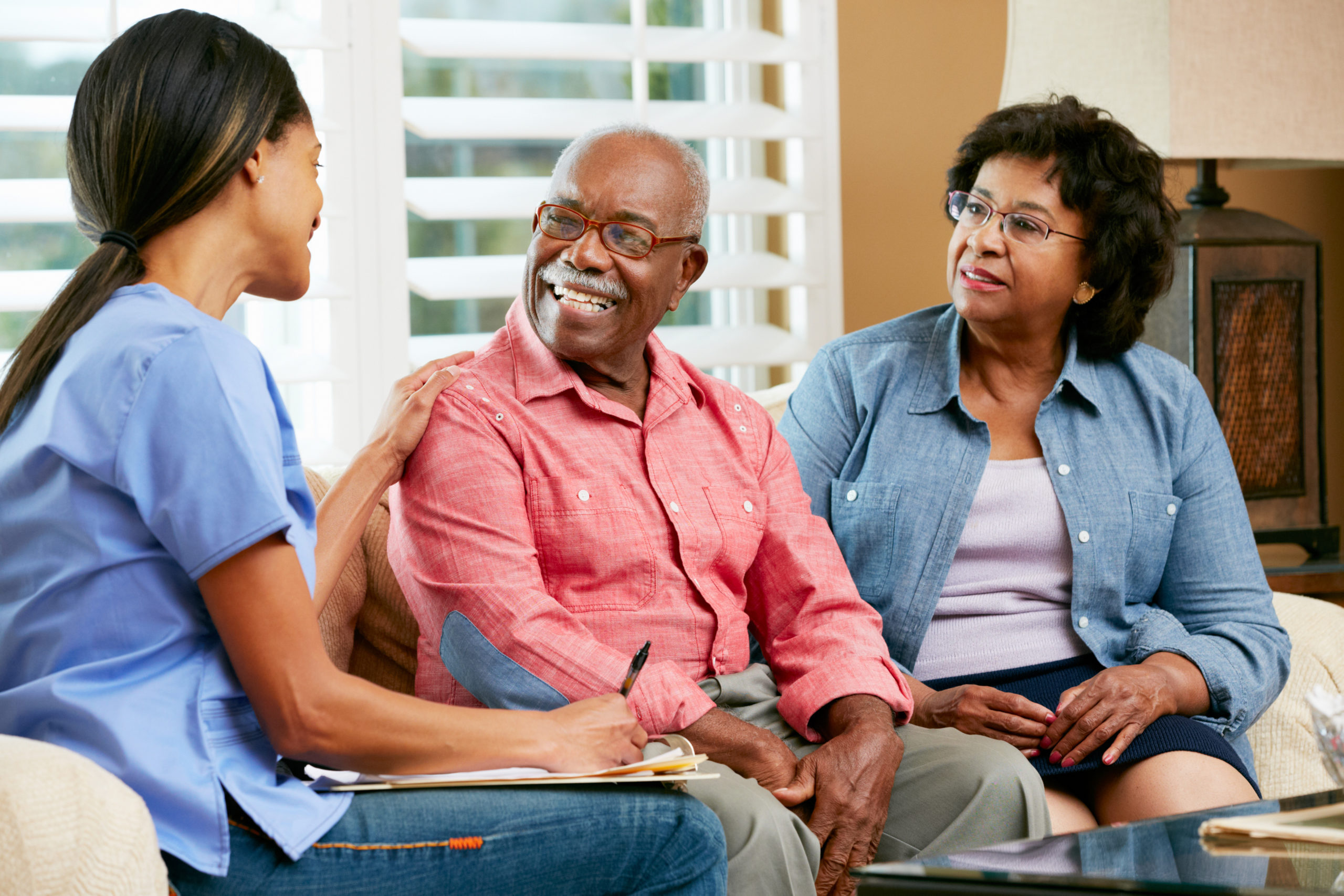 Nurse Making Notes During Home Visit With Senior Couple Smiling.
