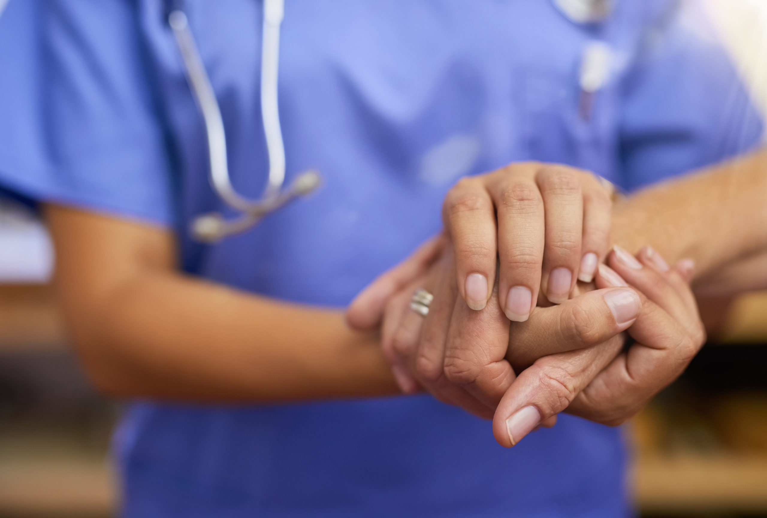Cropped shot of a nurse holding a senior woman's hands in comfort
