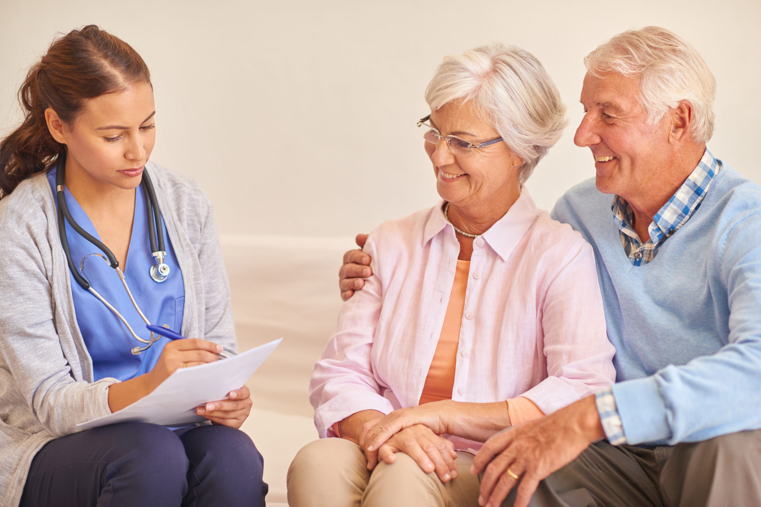 Shoot of smiling senior couple with their nurse during an appointment.