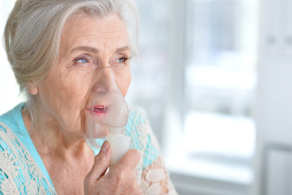 Woman breathing through a respirator.